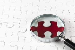 Parti mancanti di puzzle con una lente d'ingrandimento Immagini Stock Libere da Diritti