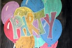 Parti och ballonger på den svart tavlan Arkivfoto