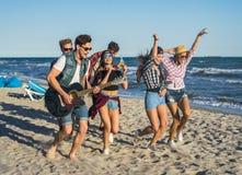 Parti på stranden med gitarren Vänner som tillsammans dansar på stranden royaltyfri fotografi