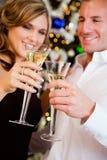 Parti: Par som rostar med Champagne By Christmas Tree Arkivbilder