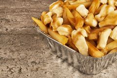 Partial close up on a poutine in a takeout container. Cooked with french fries, beef gravy and curd cheese royalty free stock image