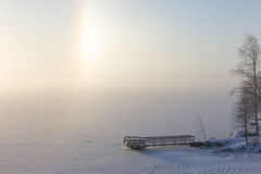 Partial halo and pier at a frozen & snowy lake Royalty Free Stock Images