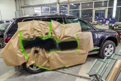 Partial painting of the side elements of the body of a black SUV royalty free stock photo
