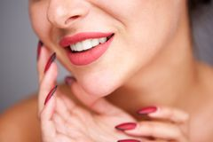 Partial portrait of woman smiling with red manicure and flawless complexion. Close up partial portrait of woman smiling with red manicure and flawless complexion stock photo