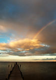 Partial rainbow over the sea at evening. A partial rainbow over the sea at evening near Middelfart, Denmark with a boardwalk running into the sea. The rainbow stock photo