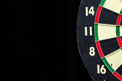 Dartboard on Black. Partial red, green, black, and cream dartboard on black with copy space on left Royalty Free Stock Photos