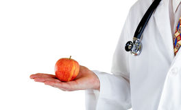 Partial side view of doctor holding apple on white background Stock Photos