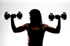 Partial Silhouette of Trainer Holding Weights. Partial silhouette of a female trainer holding dumbbells. Almost in a military press Stock Photography