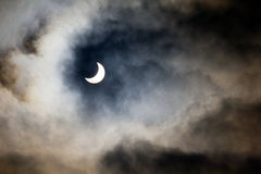Partial solar eclipse. The sun during a partial solar eclipse with dark clouds stock images