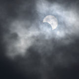 Partial solar eclipse behind the clouds Royalty Free Stock Photography