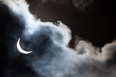 Partial solar eclipse through clouds Stock Image
