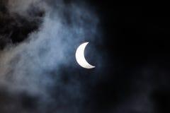 Partial solar eclipse through clouds Stock Photography