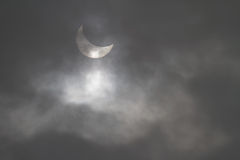 Partial solar eclipse seen through the clouds Royalty Free Stock Photography