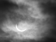 Partial solar eclipse with sun through clouds stock images