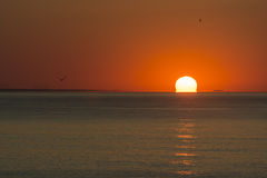 Partial sunrise from the sea, with the sun on right, orange sky and low reflection on the surface of water.  Stock Photography