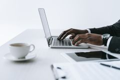 partial view of african american businessman typing on laptop at workplace royalty free stock photo