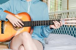 Partial view of asian girl  playing on acoustic guitar from the morning wake up in bedroom at home. A Partial view of asian girl  playing on acoustic guitar from royalty free stock photo