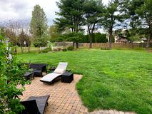 Partial view of backyard of home with glimpse of cobblestone patio and Pine Trees in background. View of backyard at home showing its landscaping and partial stock photography
