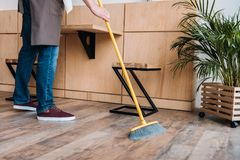 Worker cleaning floor with broom Stock Images