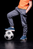 Partial view of boy standing on football ball with one leg Stock Images