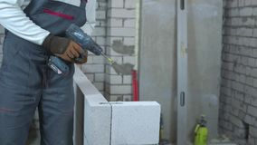Partial view of builder fixing joining clamp to blocks with electric drill. Worker building interior wall at construction site. house renovation, building and stock video