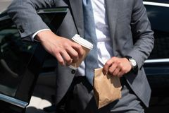 Partial view of businessman with take away food and coffee to go standing. At car royalty free stock photos