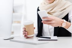 Partial view of businesswoman with coffee to go using smartphone. At workplace royalty free stock images