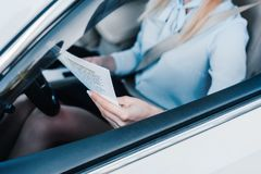 Partial view of businesswoman with newspaper on drivers seat. In car royalty free stock image