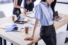 Partial view of businesswoman using smartphone and colleagues behind. In office royalty free stock image
