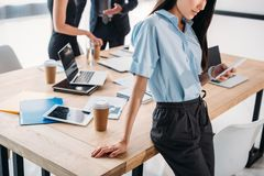 Partial view of businesswoman using smartphone and colleagues behind. In office royalty free stock photos