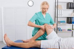 partial view of chiropractor massaging patients leg during appointment