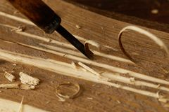 Partial view of chisel sticking in wooden plank with scobs royalty free stock photo