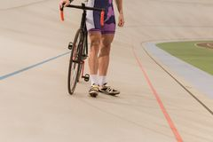 Partial view of cyclist standing near bicycle on cycle. Race track Stock Photos