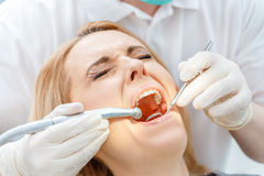 Partial view of dentist curing scared patient with closed eyes Royalty Free Stock Image