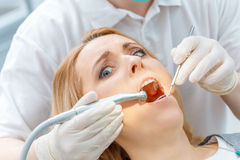 Partial view of dentist curing scared patient looking at camera Royalty Free Stock Image