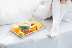 Partial view of female legs and breakfast on bed Royalty Free Stock Images