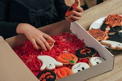 Partial view of kid arranging themed halloween cookies at wooden tabletop. At home royalty free stock photography