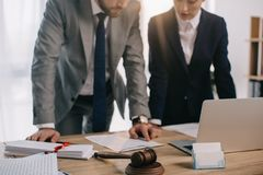 partial view of lawyers in suits working together on project at workplace with gavel and laptop royalty free stock photography