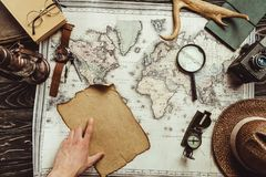 Partial view of male hand, map, blank burnt paper, watch, magnifying glass, compass and hat. On wooden surface Stock Image