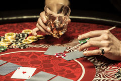 Partial view of man holding glass of whisky and poker chip at table Royalty Free Stock Image