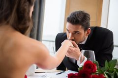 partial view of man kissing girlfirend hand on romantic date in restaurant, st valentine day stock image