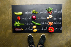 Partial view of man standing near fresh vegetables and calories table Stock Photography