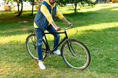 Partial view of man stylish man riding retro bicycle. In park royalty free stock photo