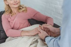 Partial view of mother and grown son holding. Hands together stock image