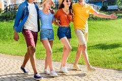 Partial view of multicultural group of friends walking on street together. On summer day stock photo