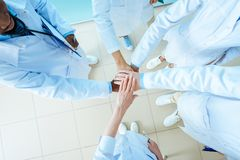 Partial view of multiracial group of doctors in lab coats holding hands,. Teamwork concept royalty free stock photo