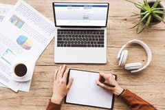 Free Partial View Of Man Making Notes In Notebook At Workplace With Laptop With Facebook Logo, Papers, Cup Of Coffee Royalty Free Stock Photos - 120659618