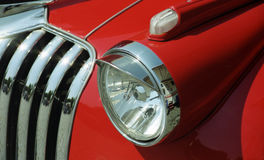 Partial view of an old red chevrolet. A partial view of a radiator grille and a headlight of an old red chevrolet Royalty Free Stock Photography