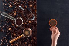 Person holding cup of coffee and roasted coffee beans with coffee pot, scoop and sugar. Partial view of person holding cup of coffee and roasted coffee beans Stock Photos