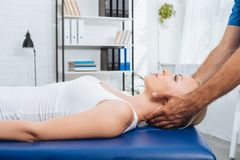 partial view of physiotherapist massaging neck of patient that lying on massage table